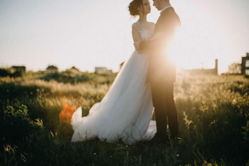 illustration photo Dj mariage avec materiel mariage wedding planner mari et femme face a face poitrine contre poitrine en corps à corps habillé dans un champ lors du couché de soleil