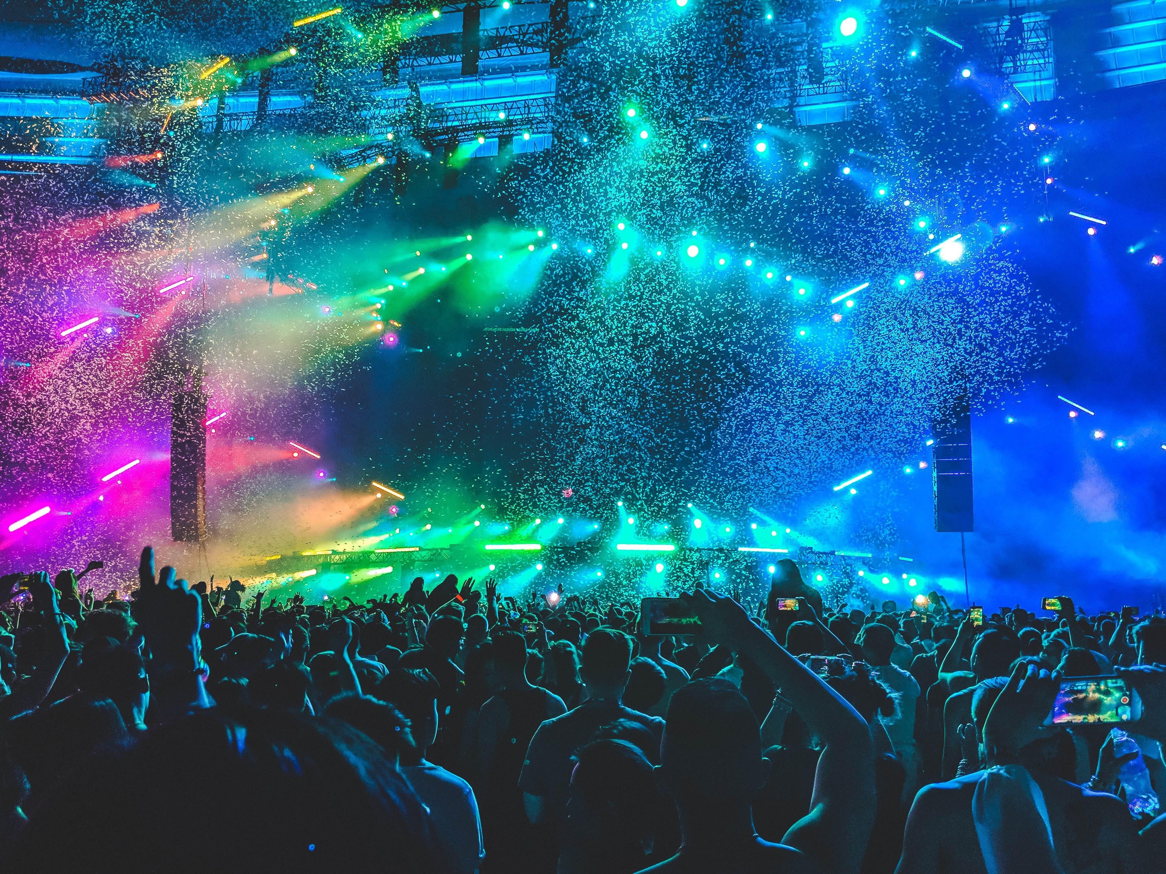 photo illustarant un festival musique DJ a l interieur du public prise de vue face à la scène avec des jeux de lumiere rose orange vert bleu violet en degradé