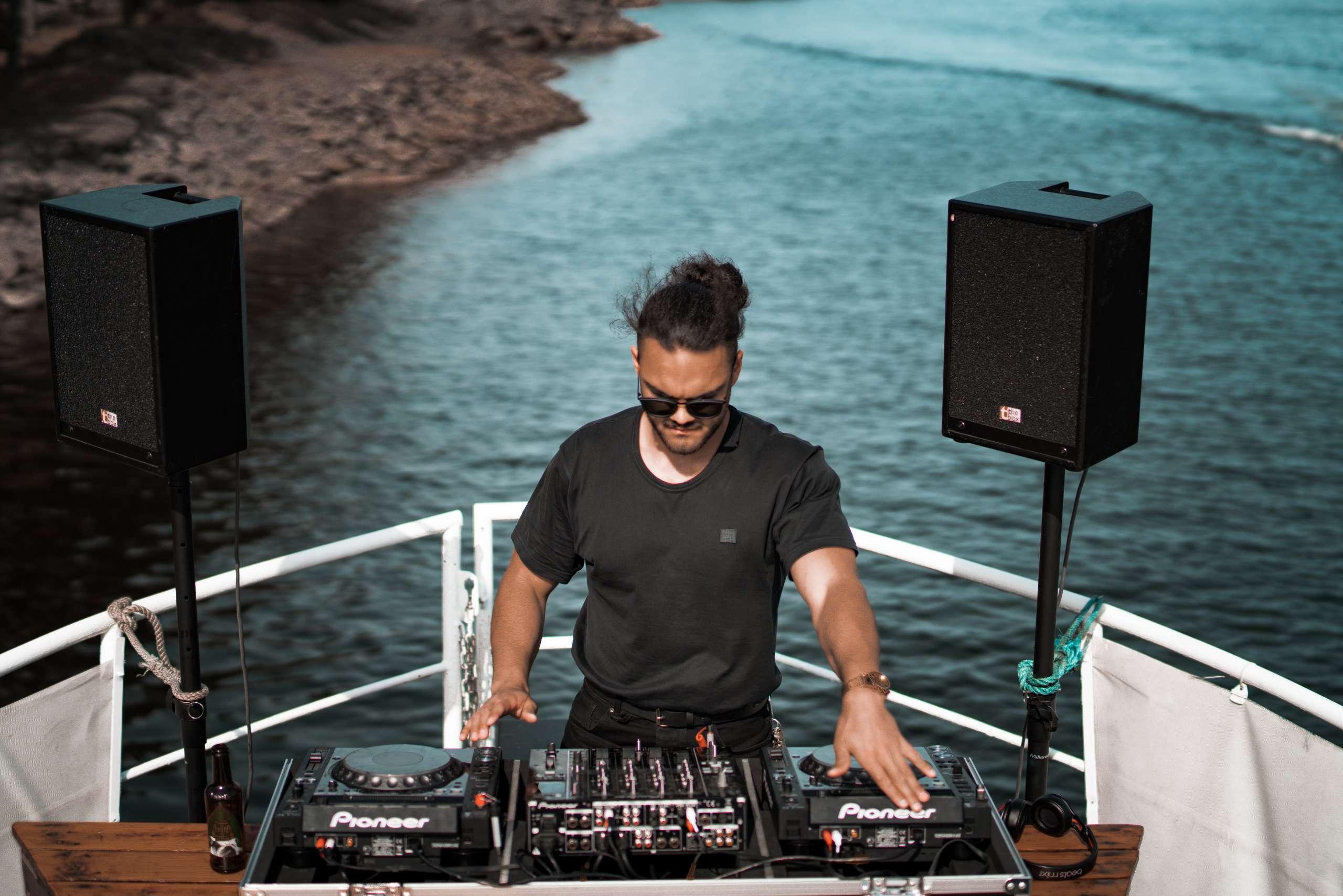 un homme en tee shirt noir mix pour une soirée Boat Party à Cannes - French Touch Dj à Nice